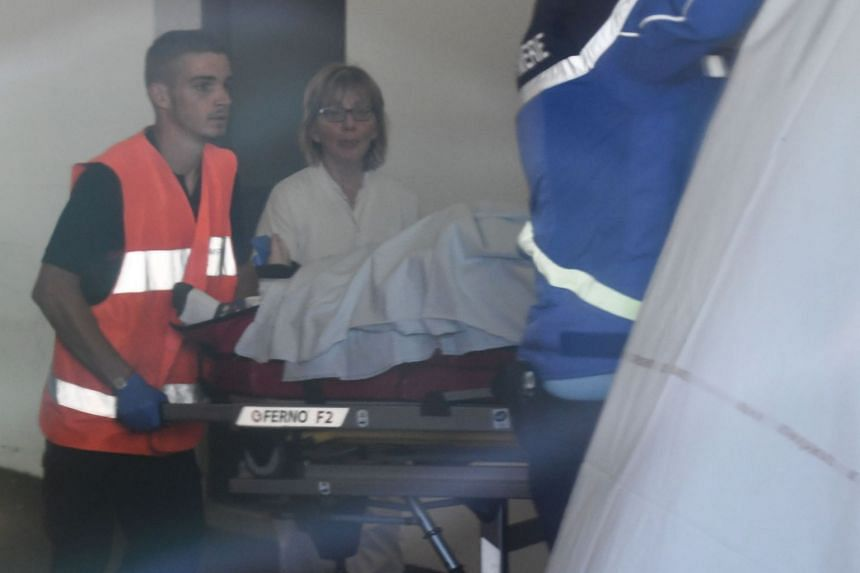 Rescue workers are seen through a window as they transport Froome on a stretcher upon arrival at a hospital.