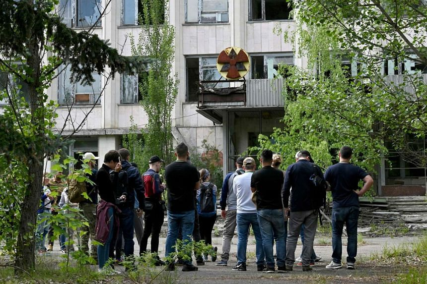 Visitors listen to a guide's information in the ghost city of Pripyat during a tour of the Chernobyl exclusion zone.