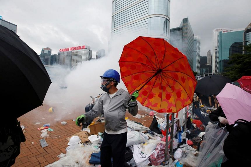 A protester holds an umbrella near tear gas fired by Hong Kong police during a demonstration against a proposed extradition bill, in Hong Kong, China on June 12, 2019.