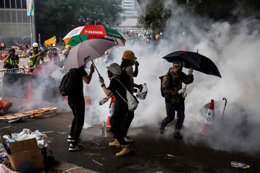 Tear gas fired by police surrounds protesters during a rally against a controversial extradition law proposal outside the government headquarters in Hong Kong on June 12, 2019.