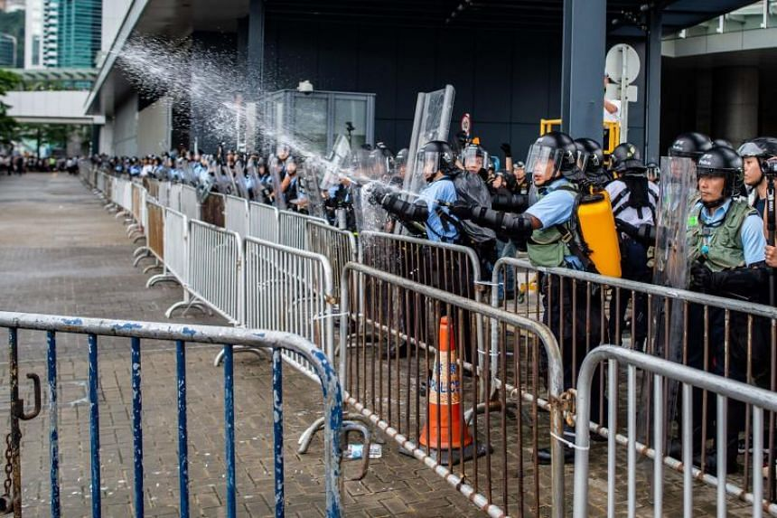 Police officers use pepper spray as protesters occupy the space outside the Legislative Council in Hong Kong on June 12, 2019.
