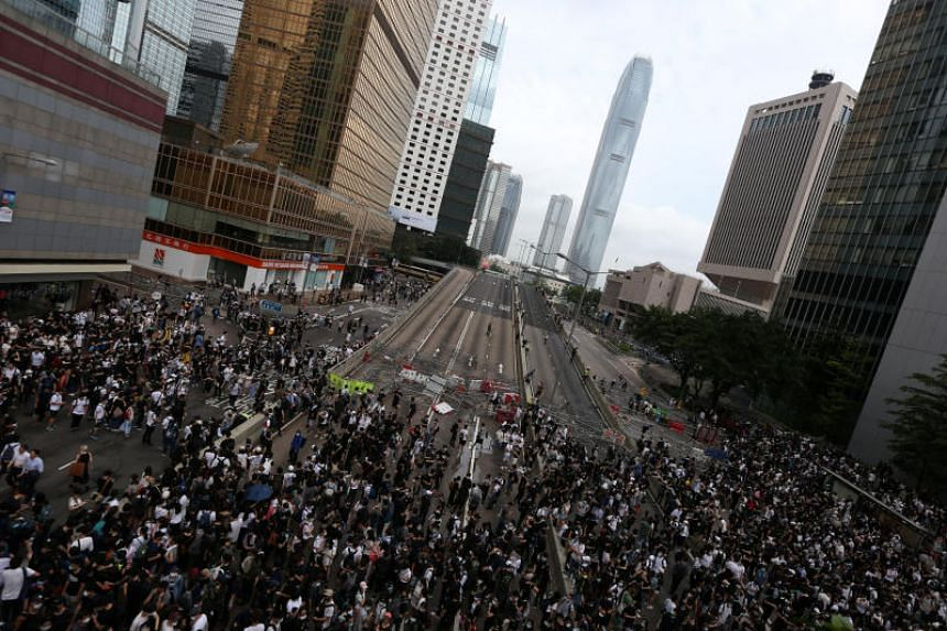 Protesters march along a road demonstrating against a proposed extradition Bill in Hong Kong on June 12, 2019.