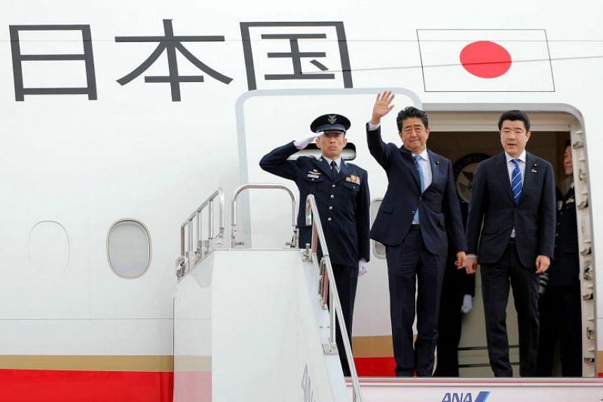 Japan's Prime Minister Shinzo Abe waves upon his departure for Teheran at Haneda airport in Tokyo on June 12, 2019.