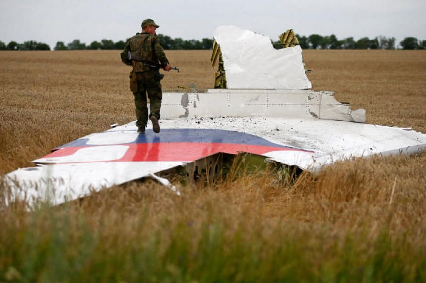 An armed pro-Russian separatist stands on part of the wreckage of the Malaysia Airlines MH17 plane after it crashed near the settlement of Grabovo in the Donetsk region, on July 17, 2014.