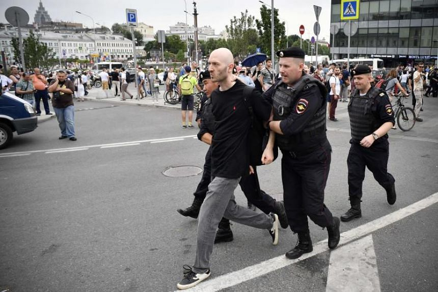 Russian police officers detain a protester during a march to protest against the alleged impunity of law enforcement agencies in central Moscow on June 12, 2019.