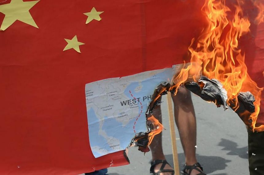 Activists burn a mock Chinese flag with a map of the South China Sea during a protest in front of the Chinese consulate in Manila on June 12, 2019.