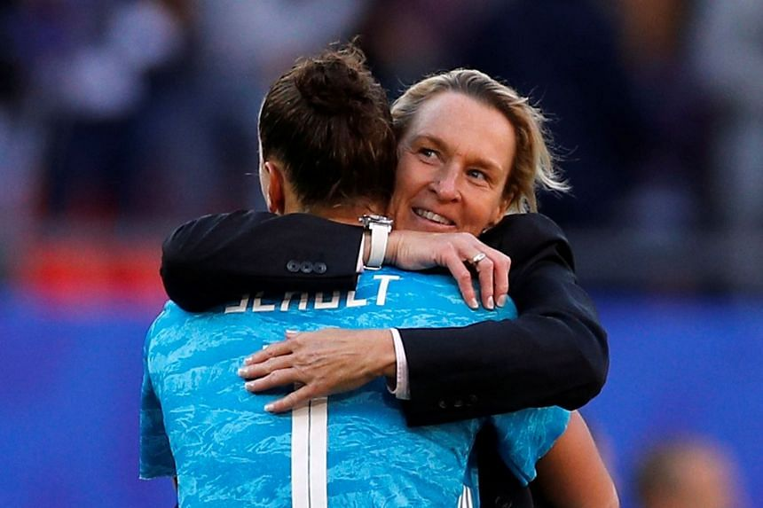 Germany coach Martina Voss-Tecklenburg and Germany's Almuth Schult celebrate after the match.
