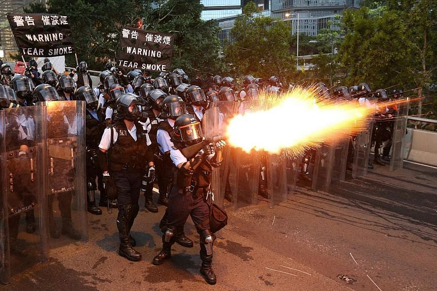 Protesters fleeing as police fired tear gas at a rally near the government headquarters. Some wore masks to protect themselves. Protesters threw water bottles, bricks and other items at riot police and chanted slogans, vowing to stay put until the Bi