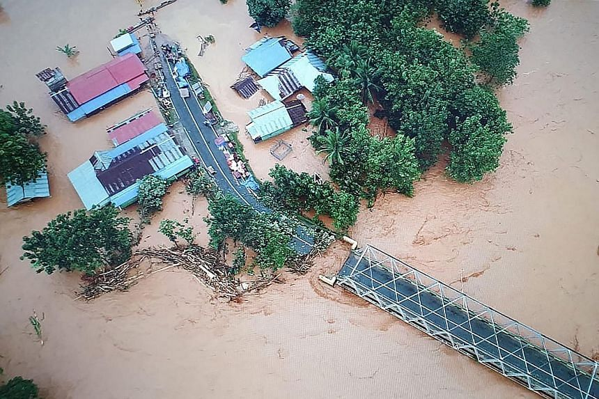 A pickup truck making its way through a flooded village in Andadowi in South-east Sulawesi on Tuesday. Below is a handout picture released by Indonesia's accident mitigation agency showing an aerial view of the village. PHOTOS: AGENCE FRANCE-PRESSE
