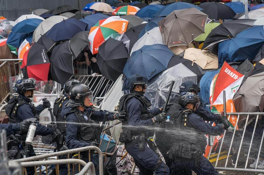 Police officers seen using pepper spray against protesters during a protest against a controversial extradition law proposal, outside Hong Kong government headquarters on June 12, 2019.