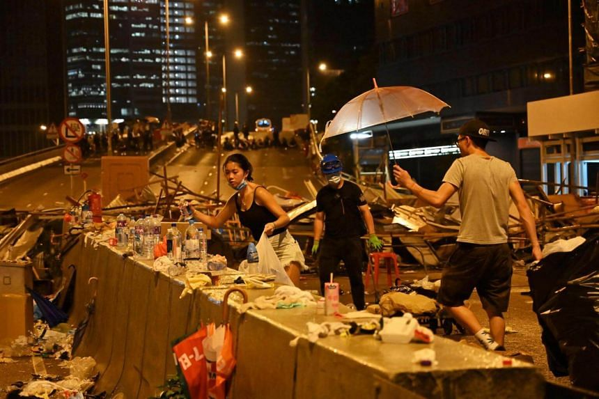 Demonstrators clean a street they occupied in Hong Kong, on June 12, 2019.