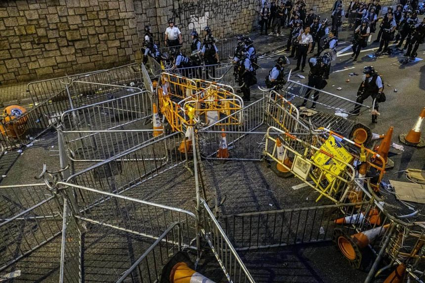 Riot police dismantle barricades set up by protesters outside the Legislative Council in Hong Kong on Wednesday night (June 12).
