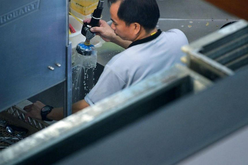 A kitchen worker washing cutlery under a running tap at a cafe in Raffles Place.