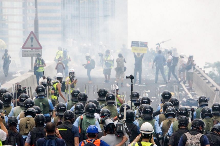Police officers fire tear gas towards protesters during a protest against a controversial extradition law proposal, outside Hong Kong government headquarters, on June 12, 2019.