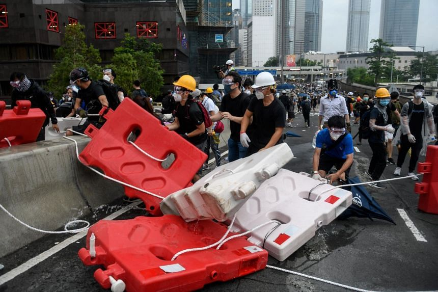 Protesters set up barricades during a rally against an extradition Bill near the Legislative Council in Hong Kong, on June 12, 2019.