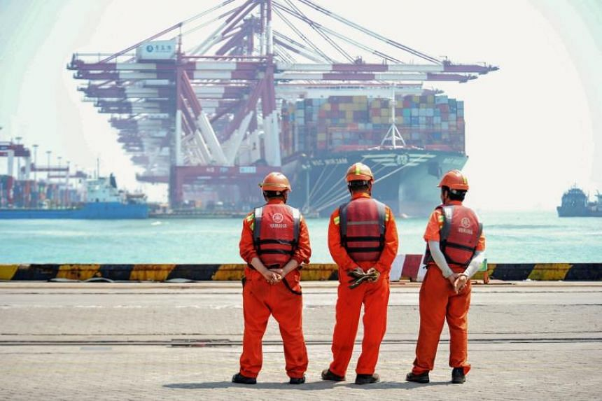 Staff members stand at a port in Qingdao, in China's eastern Shandong province on June 10, 2019.
