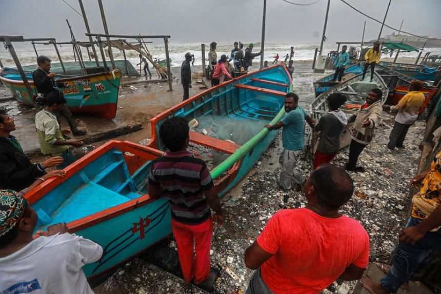 Indian fishermen move a fishing boat to a safer place along the Arabian sea coast, as Cyclone Vayu approaches Veraval, India, on June 13, 2019.