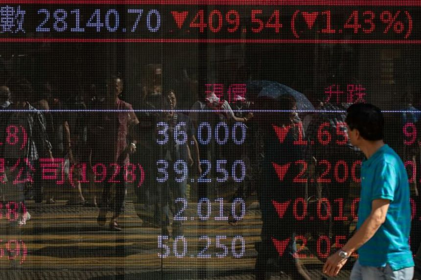 A man walks past an electronic board displaying exchange rates in Hong Kong on May 14, 2019.