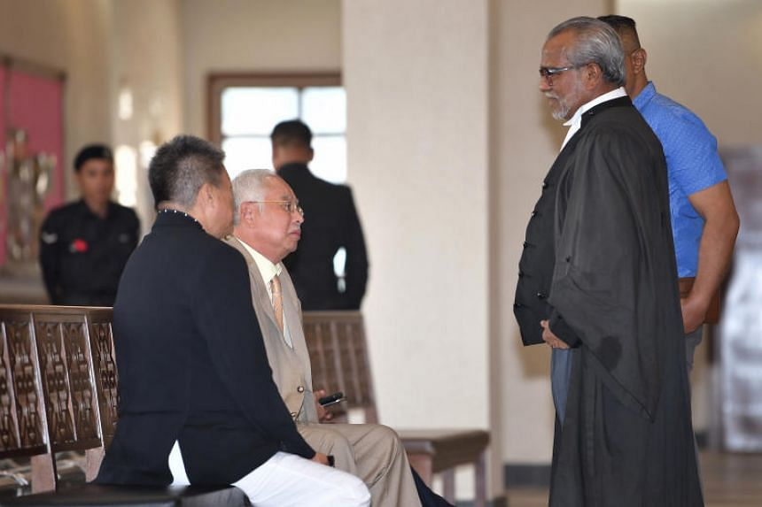 Former Malaysian premier Najib Razak (seated) on June 10, speaking to the main defence lawyer, Tan Sri Muhammad Shafee Abdullah (in black, standing), during a court recess at the ongoing SRC International trial, at the Kuala Lumpur High Court.