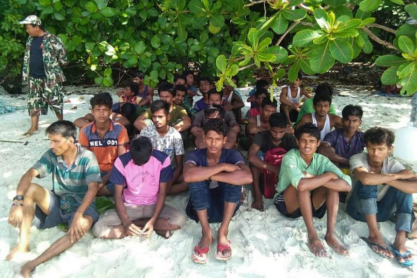 A group of Rohingya Muslims sitting on the sand at the Tarutao Marine National Park on Rawi island, southern Thailand on June 11, 2019.