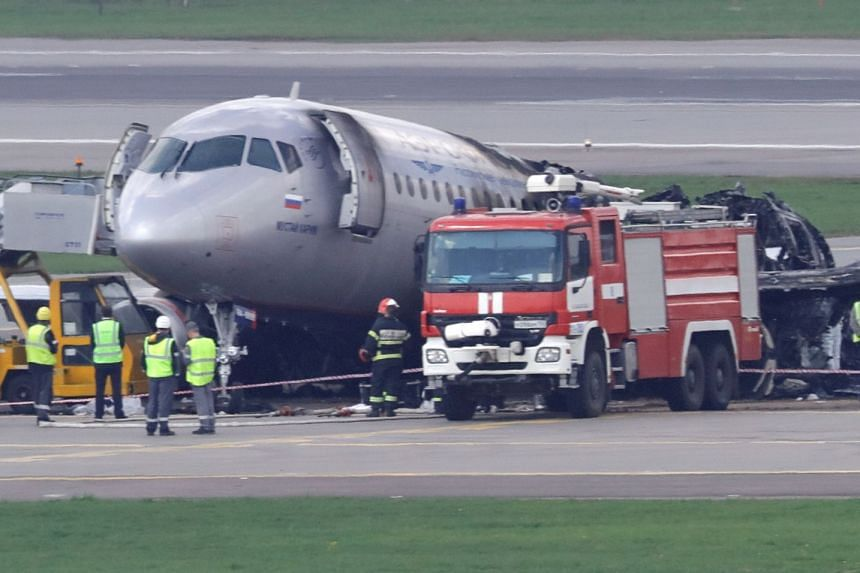 Members of the emergency services and investigators work at the accident scene at Moscow's Sheremetyevo airport.