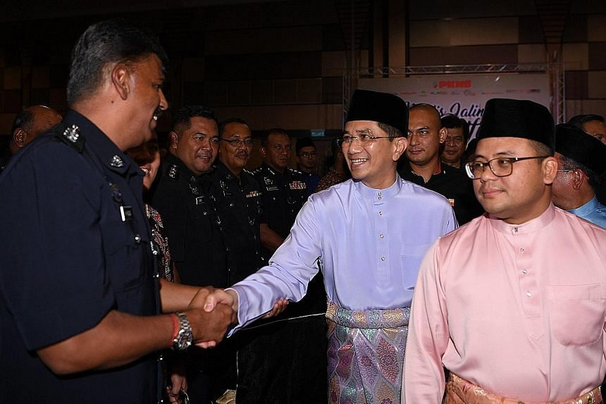 Mr Muhammad Haziq Abdul Aziz (above) claims that Economic Affairs Minister Azmin Ali tried to cover up their three-year relationship. Datuk Seri Azmin (centre), with Selangor Menteri Besar Amiruddin Shari, shaking hands with police officers at a Hari