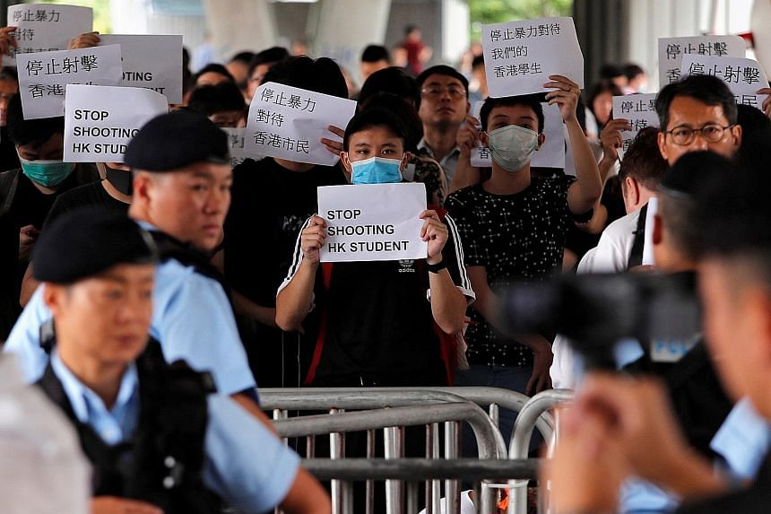 Protesters holding up signs in Hong Kong yesterday, after the huge rally over the extradition Bill on Wednesday sparked violent clashes between protesters and the police that left 81 people injured and saw 11 arrests. Hong Kong police officers conduc