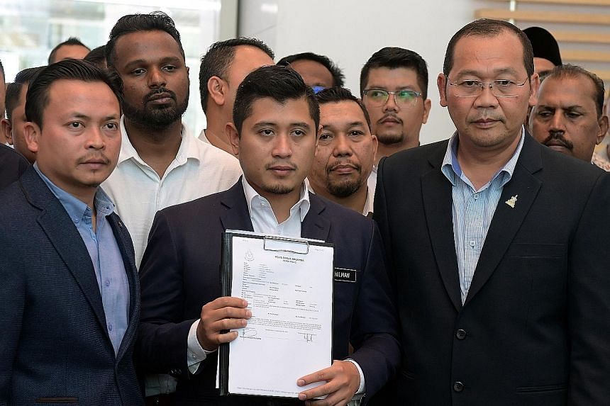 Economic Affairs Minister Azmin Ali's political secretary Hilman Idham holding up a copy of the police report he made yesterday. He had asked the police to investigate the sex videos purportedly showing Malaysian government official Muhammad Haziq Ab