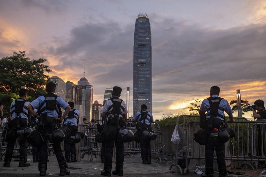 Police officers stand guard in Hong Kong on June 13, 2019, after violent protests.