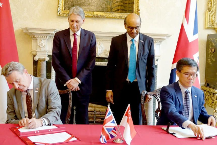 Britain's Government Digital Service director Kevin Cunnington and GovTech chief executive Kok Ping Soon sign a memorandum of understanding to deepen collaboration and exchange in the development of Digital Government Services. Witnessing the signing