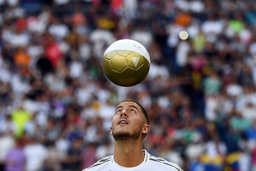 Hazard plays with a ball during his official presentation.