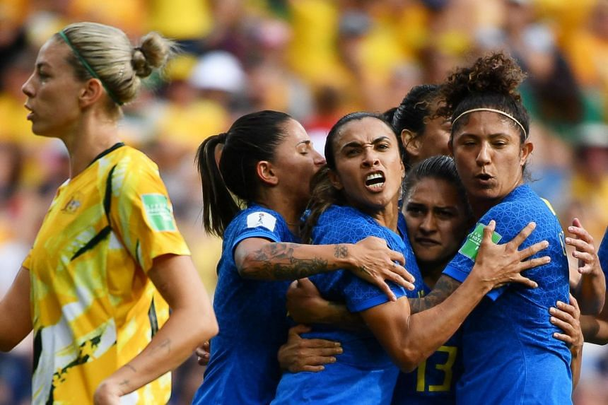 Brazil's forward Marta (centre) celebrates with team mates after scoring a goal.