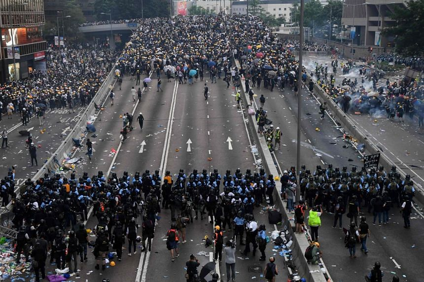 Protesters face off with police after they fired tear gas during a rally against a controversial extradition Bill in Hong Kong on June 12, 2019.