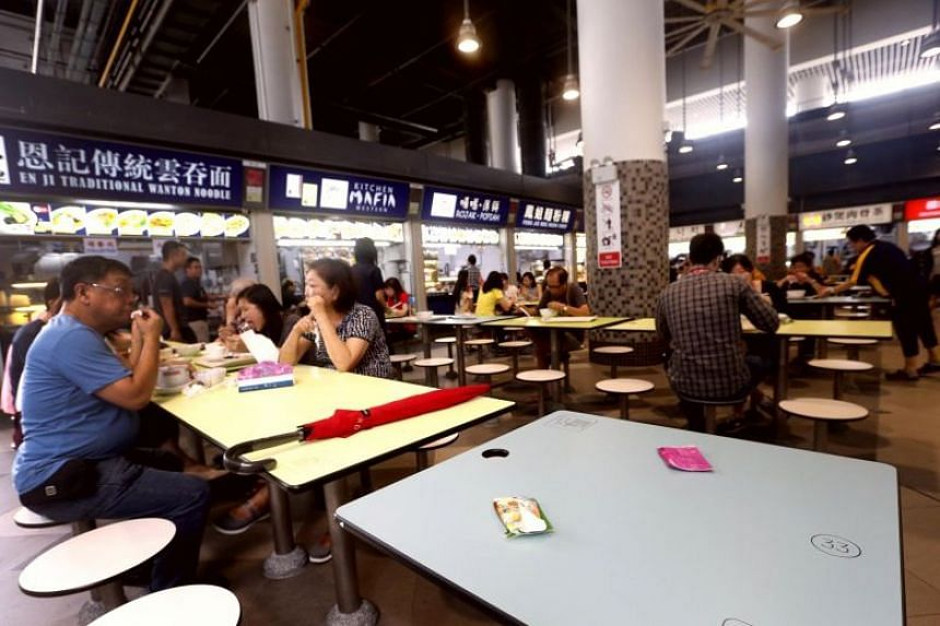"Diners ""choping"" tables and seats at a hawker centre."