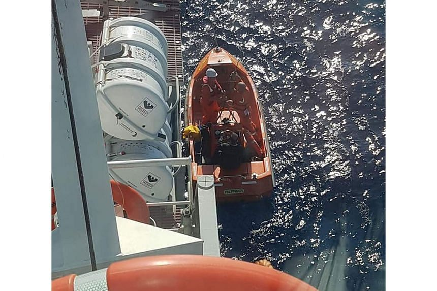 Mr Low in the Diogo Cao's rescue boat with some of the ship's crewmen. First Officer Srdan Bazdan had spotted a bright orange ring buoy floating about 1km away and when the ship neared, they found Mr Low. The RSAF Rescue 10's Aircrew Specialist Nicol