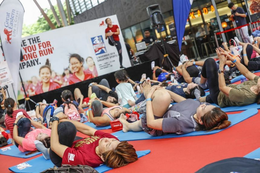 Fifty women doing a stretching exercise led by fitness trainer Roxanne Gan at the launch of the Great Eastern Women's Run yesterday.