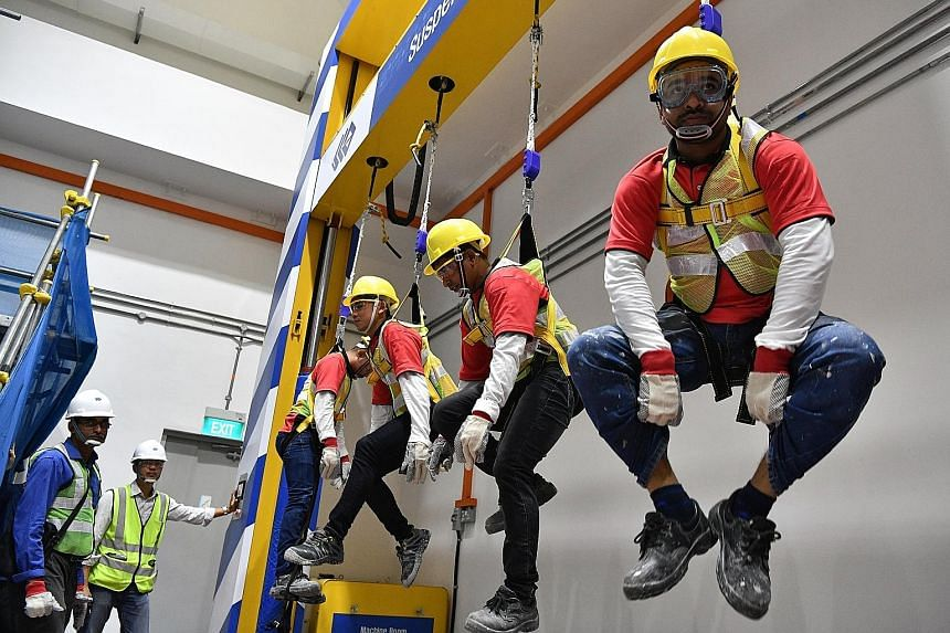 Workers trying out the suspension trauma simulator at the new construction safety school in JTC Space @ Gul. From next month, workers, including supervisors, on all new projects by developer JTC will attend courses at the $2.2 million school. ST PHOT
