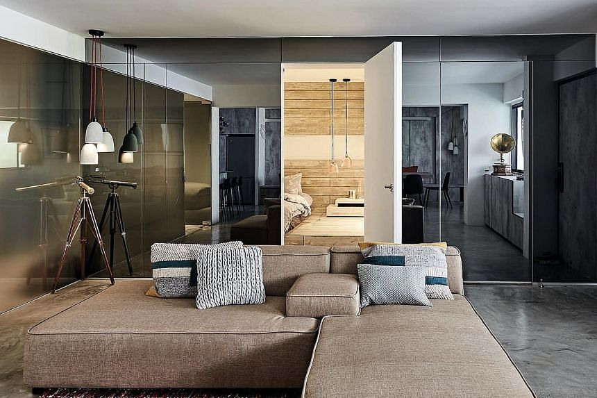 The concrete screed floor gives the flat an industrial vibe, which is complemented by a contemporary sofa and sleek tinted mirror doors.