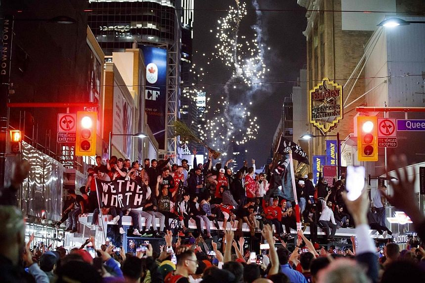Toronto Raptors fans celebrate atop a bus after their team beat the Golden State Warriors in Game 6 of the NBA Finals to clinch their maiden title on Thursday night.