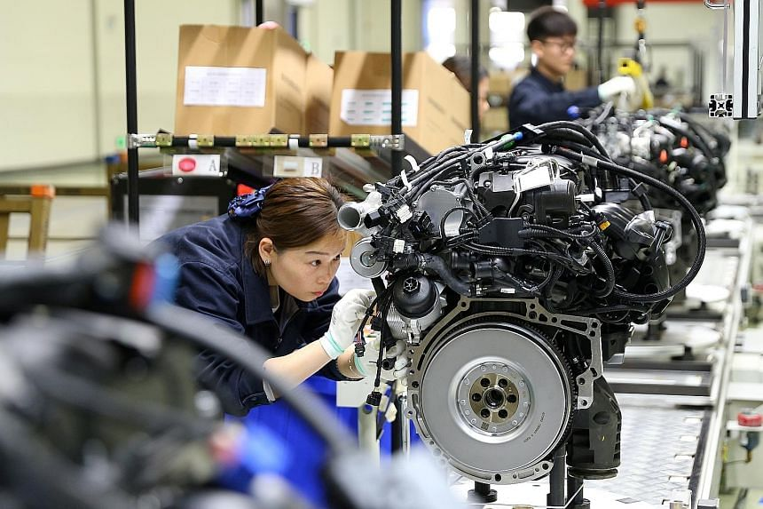 An employee at an automotive engine factory in China's Sichuan province. Industrial output grew 5 per cent last month from a year earlier, missing analysts' expectations of 5.5 per cent. PHOTO: REUTERS