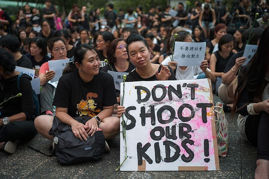 A group of mothers at a rally in Hong Kong yesterday. They started an online petition, signed by tens of thousands, to voice their disagreement with Chief Executive Carrie Lam, who had called the protesters spoilt children. Police standing guard near