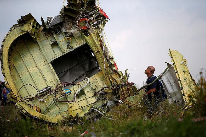 A Malaysian investigator inspecting the crash site of Malaysia Airlines Flight MH17 in 2014. The plane was shot down in July that year, killing all 298 people on board. An investigation team formed after the disaster is set to brief families of the v