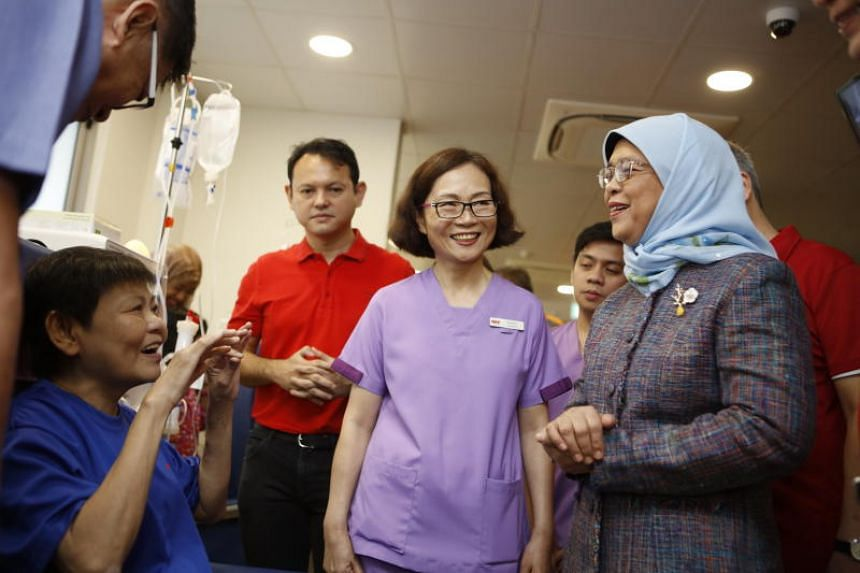 President Halimah Yacob speaking to kidney patient Lau Heng Ing at the new dialysis centre at Block 204 Marsiling Drive during its launch on June 15, 2019. Minister of State for Manpower and National Development Zaqy Mohamad was also among those pres