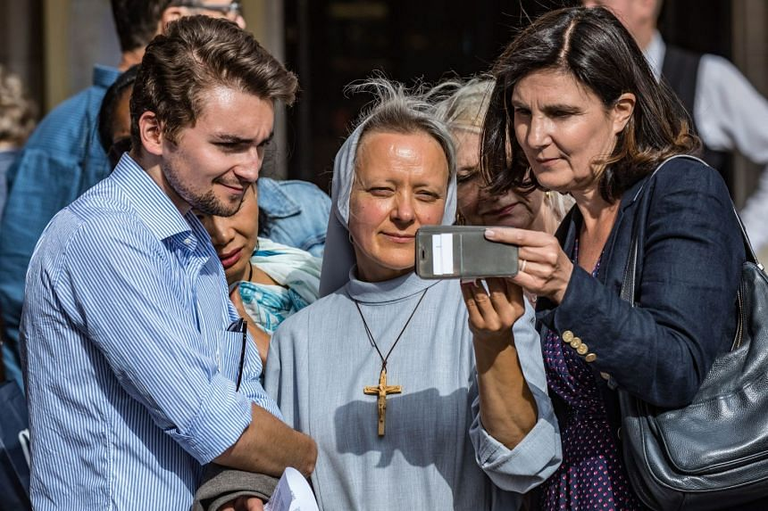 A nun and worshippers watch the mass displayed on a cellphone in front of Notre-Dame.