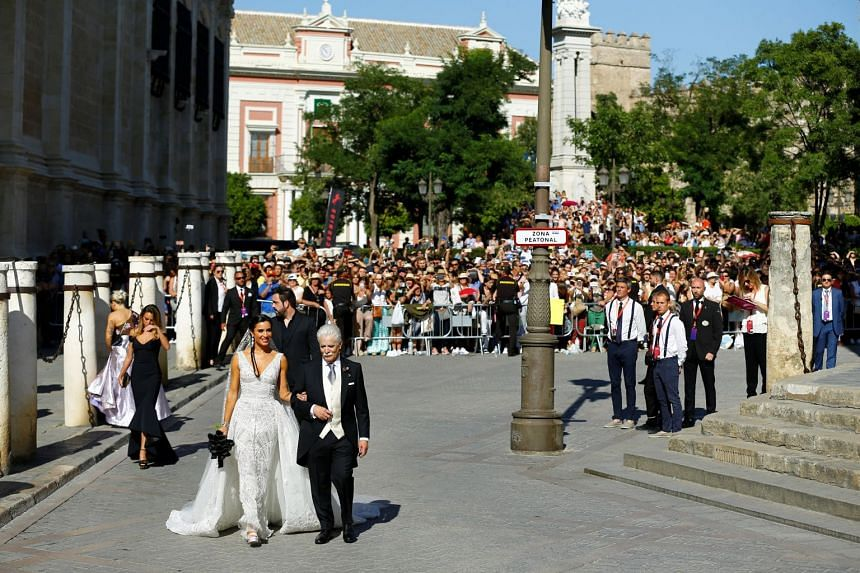 Pilar Rubio walks with her father Manuel Rubio for her wedding.