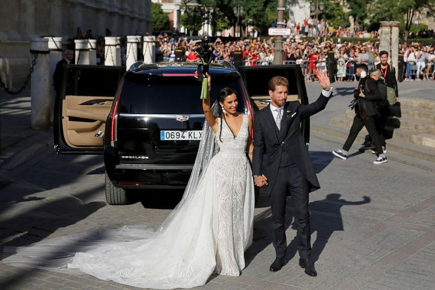 Real Madrid captain Sergio Ramos and his wife Pilar Rubio wave after their wedding at the cathedral in Seville, Spain.