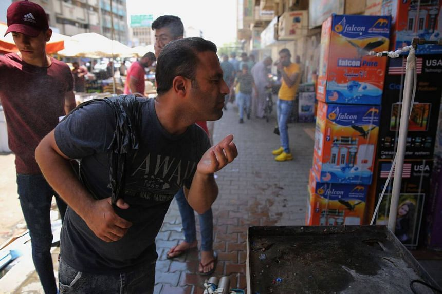 An Iraqi man uses a curbside shower to cool off during a heatwave in the capital Baghdad, on June 14, 2019.