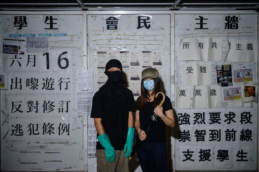 Two student protesters posing with protective rubber gloves and an umbrella during an interview with AFP in Hong Kong, who took part in the protests on June 12, 2019.