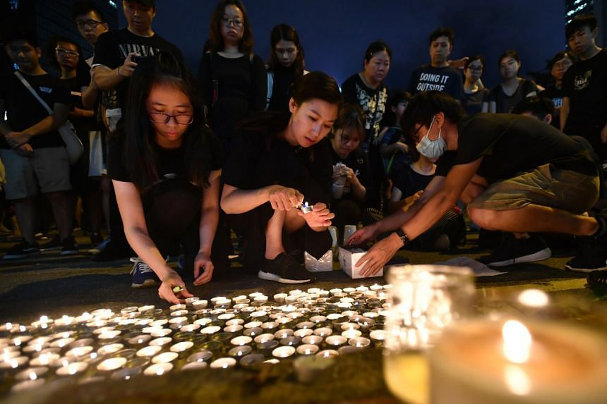 Protesters lighting candles on June 16 outside Pacific Place, where a man died reportedly while protesting the extradition Bill.