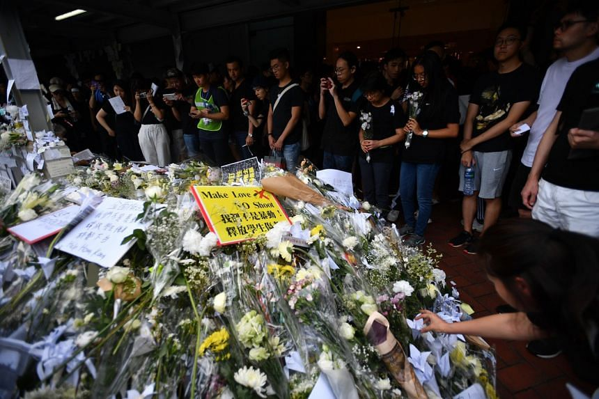 People leaving flowers at a memorial in honour of a protester who died during a protest against the controversial extradition Bill, in Hong Kong on June 16, 2019.
